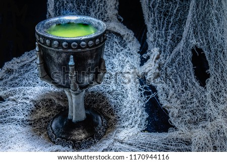 Witch's potion in a pewter goblet with finger bone stem. #1170944116
