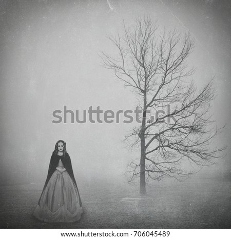 Witch standing in foggy landscape with lonely tree. Halloween textured background #706045489