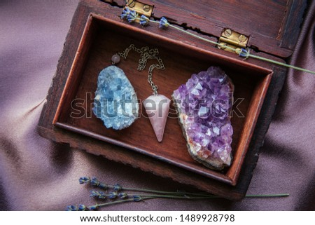 Witch tools inside beautiful old wood box. Rose quartz pendulum, natural amethyst and celestite crystal clusters. Dry lavender flowers on dark purple cloth. Alternative lifestyle concept. #1489928798