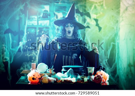 Witch with awfully face and hat on her head in creepy surroundings full of cobweb sends evil. Halloween concept. #729589051
