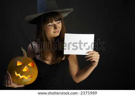 Witch with isolated white card and a pumpkin