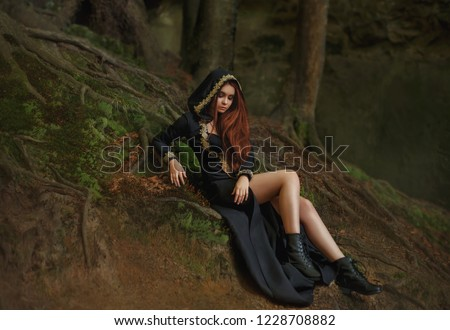 Stock Photo witch with red hair in a long black dress with open legs, hooded cloak, leather boots stands in the foggy forest with rays of moonlight. pretty dark elf from medieval ages. art photo, creative colors