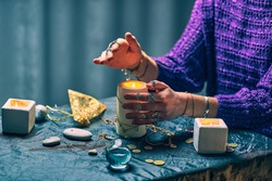 Witch woman uses candles for magic spell during mystical witchcraft, sorcery and occult divination