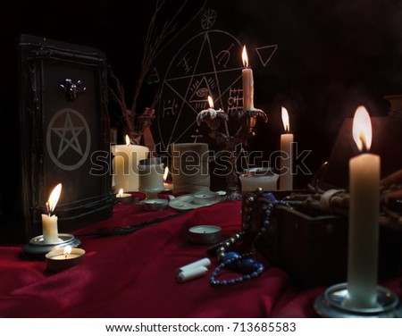 Witchcraft composition with burning candles, magic book, quill, jewelry, chalk and pentagram symbol. Halloween and occult concept, black magic ritual.  #713685583