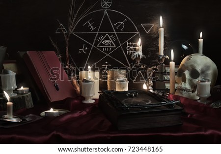 Witchcraft composition with human skull, candles, magic book and pentagram symbol. Halloween and occult concept, black magic ritual. #723448165