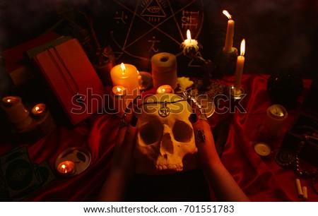 Witchcraft composition with witch's hands holding a human skull, candles, magic books, tarot cards, amulets and pentagram symbol. Halloween and occult concept, black magic ritual.  #701551783