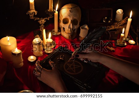 Witchcraft composition with witch's hands holding a quill, satanic magic book with pentagram symbol, human skull and candles. Halloween and occult concept, black magic ritual.  #699992155