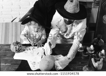 Witcher and little magician get ready for Halloween. Guy and kid with busy faces in hats draw and decorate pumpkins. Man and boy in room on white brick wall background. Halloween and holiday concept. #1151934578