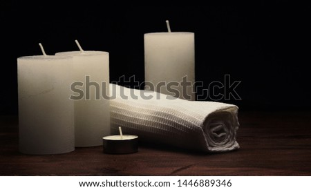 wite napking and candles on wooden surface in composition, spa, relax, cosy ambience, equilibrium concept