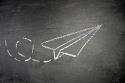 With a chalk drawn a paper plane and a dashed way on a dark marble surface - background with a flying paper plane