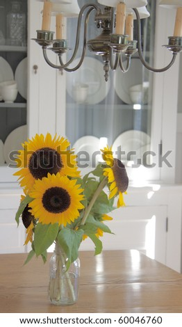 With a china hutch in the background and a chandelier overhead, the arrangement of sunflowers in a simple jar contrasts beautifully