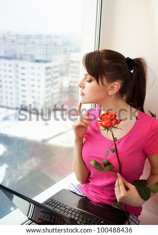 with a rose and the laptop on a window sill - stock photo