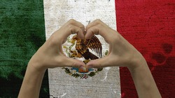 With a stylized Mexican flag background an anonymous person's hands being held in the form of a heart, symbolizing love and patriotism for Mexico.