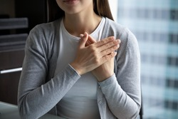 With all my heart! Close up of young lady hands folded close to heart in peaceful candid sincere sign gesture appreciating destiny god for help, expressing heartfelt thank you to friend mate colleague