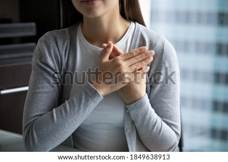 With all my heart! Close up of young lady hands folded close to heart in peaceful candid sincere sign gesture appreciating destiny god for help, expressing heartfelt thank you to friend mate colleague Stock photo ©
