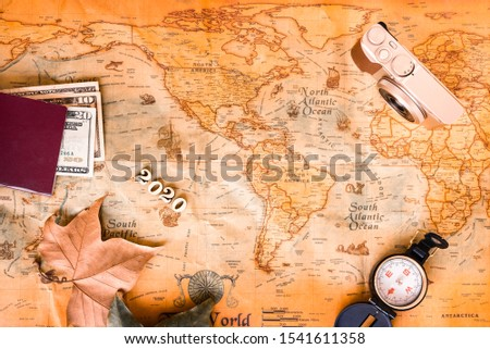 With an old background map and travel accessories, we plan our tourist destinations for 2020. #1541611358