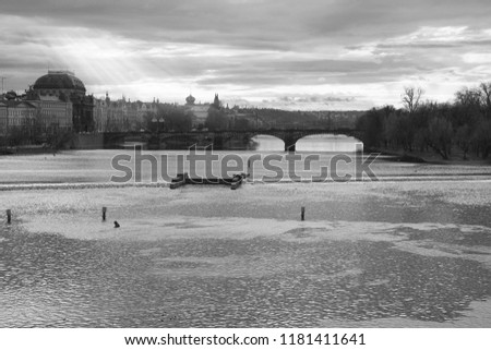 With Charles Bridge and New Town district of Prague in the background, a beautiful landscape of Vltava River in black and white with sun rays spreading through the clouds #1181411641