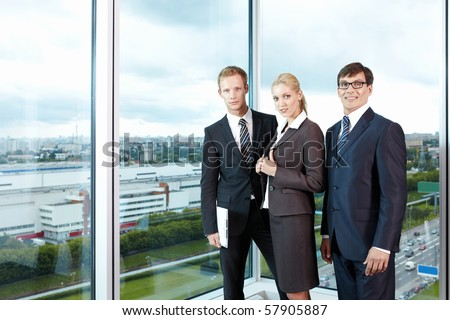 With employees in suits against the big window office