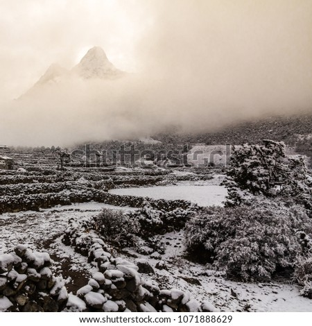 With fresh snow covering rock walls and fields in the foreground, the unique and iconic shape of Ama Dablam mountain appears briefly through a gap in the cloud above the snowy, monochromatic scene #1071888629