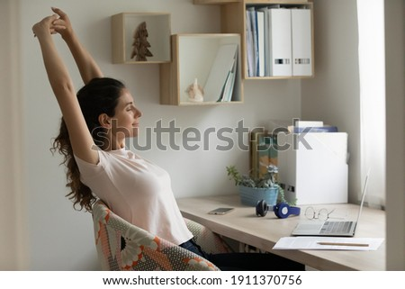 With great relish. Serene female student relaxing after long time of distant learning by laptop at home office. Happy young woman satisfied with finishing work on pc stretch muscles lean back on chair