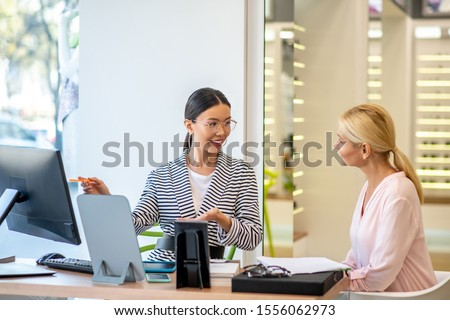 With high quality. Appealing blonde-haired doctor helping young assistant do the work with high quality and in short terms
