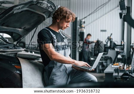 With laptop. Adult man in grey colored uniform works in the automobile salon.