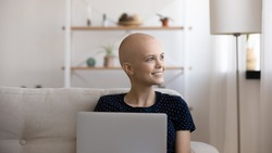 With light in eyes. Happy young female suffering from oncology get email from clinic about donor match. Amazed woman sick with cancer look aside of pc screen glad of positive dynamic in test results