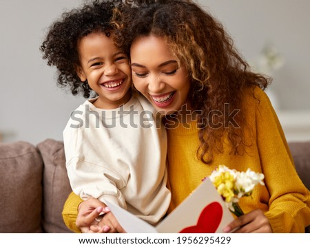 With love. Cute excited little boy son giving his mom handmade greeting postcard with red heart, happy mother embracing with with child while sitting on sofa at home. Mothers day celebration concept Stock foto ©