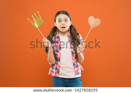 With no expectation of reward. Little girl holding prop crown and heart on stick as favorite reward. Cute mini miss beauty pageant winner enjoying reward for success. Awarding with prize and reward. #1427858195