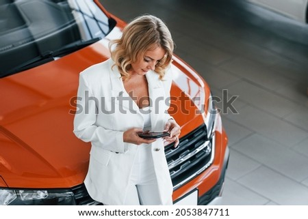 With phone in hand. Woman in formal clothes is indoors in the autosalon.