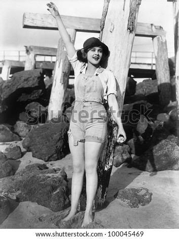 With sand between her toes, a young woman waves on the beach