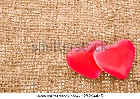 with two red hearts symbol of candy with  needle on fabric sack texture background