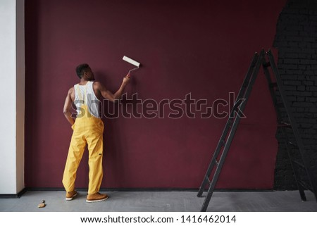 With white platen in hands. Young african american worker in the yellow uniform have some job. Stockfoto ©