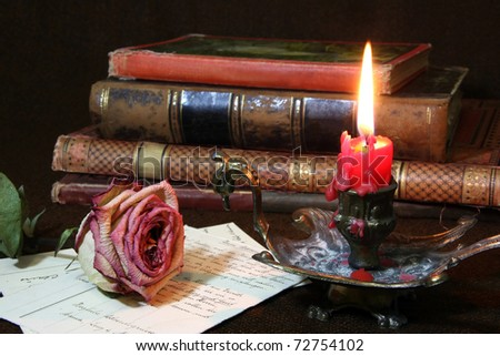 Withered, dry rose with candle flame and antique books - low-key tone, focus on the rose texture