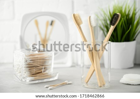 Without plastic concept. Eco friendly bathroom accessories. Bamboo toothbrushes, cotton pads and cotton buds on a light gray table. Zero waste. Copy space, Horizontal orientation. Foto stock ©