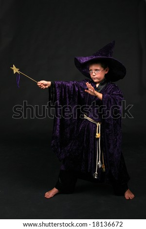 wizard boy in purple velvet hat and robe holding wand and casting a spell