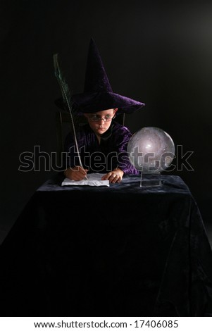 wizard boy looking into crystal ball and writing with a feather pen