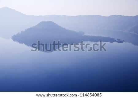 Wizard Island in Crater Lake on a hazy day with reflections and copy space - stock photo