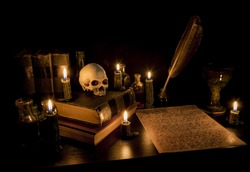 Wizard's Desk. A desk lit by candle light. A human skull, old books, a goblet, and potion bottles are present. Desk has parchment paper with arcane writing. Feather pen in inkwell. Focus on skull.