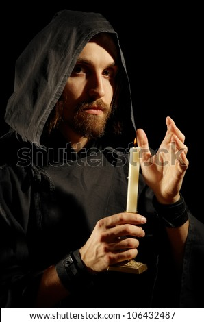 wizard with burning candle in dark room