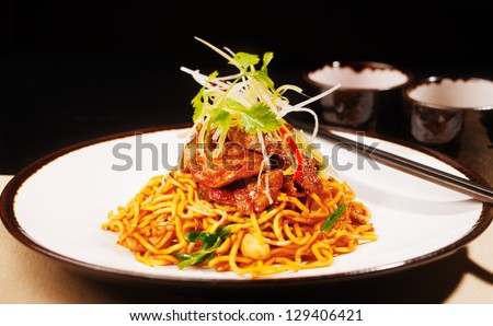Wok fried Szechwan chicken on a bed of noodles is a typical Chinese dish