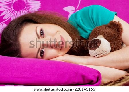 Woken up beautiful girl in bed with a soft toy. Smiling girl in the bed close-up. Brunette with brown eyes. Beauty portrait of young woman