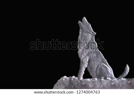 wolf in silhouette howling to the full moon, wolf in silhouette howling to the full moonhe wolf howls at the moon. Night.