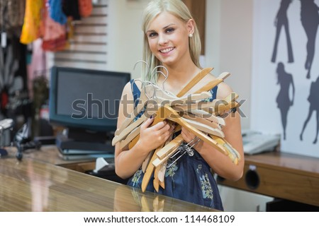 Woma standing behind counter holding hangers in boutique