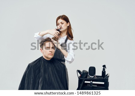 woman a hairdresser in an apron do a hairdress to a young man in a black peignoir on a light background cropped view