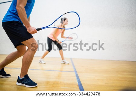 Woman about to serve the ball in the squash court