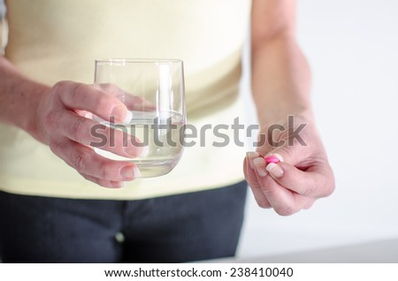 Woman about to take a pill with a glass of water - Shutterstock ID 238410040