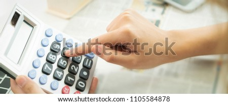 Woman accountant, office worker or bank worker uses calculator to calculate business profit and loss account. She presses number 6 on the calculator. Horizontal web banner style.