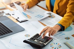 Woman accountant use calculator and computer with holding pen on