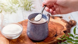 Woman adding collagen powder to her morning coffee. Beauty collagen supplement, additional collagen intake